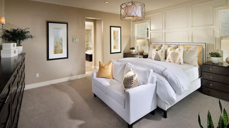 Một ánh sáng mặt dây chuyền trống thời trang chiếu sáng phòng ngủ chính màu be này tự hào với chiếc giường màu trắng và tình yêu tương phản với đầu giường và tủ quần áo bằng gỗ tối màu.