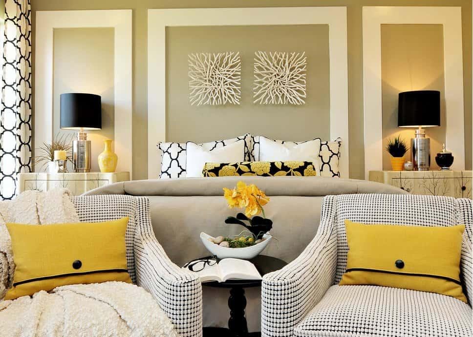 Một cặp nghệ thuật treo tường gỗ lũa treo phía trên giường trong phòng ngủ chính tuyệt vời này với đèn bàn màu đen và ghế bành có hoa văn làm nổi bật với gối màu vàng.