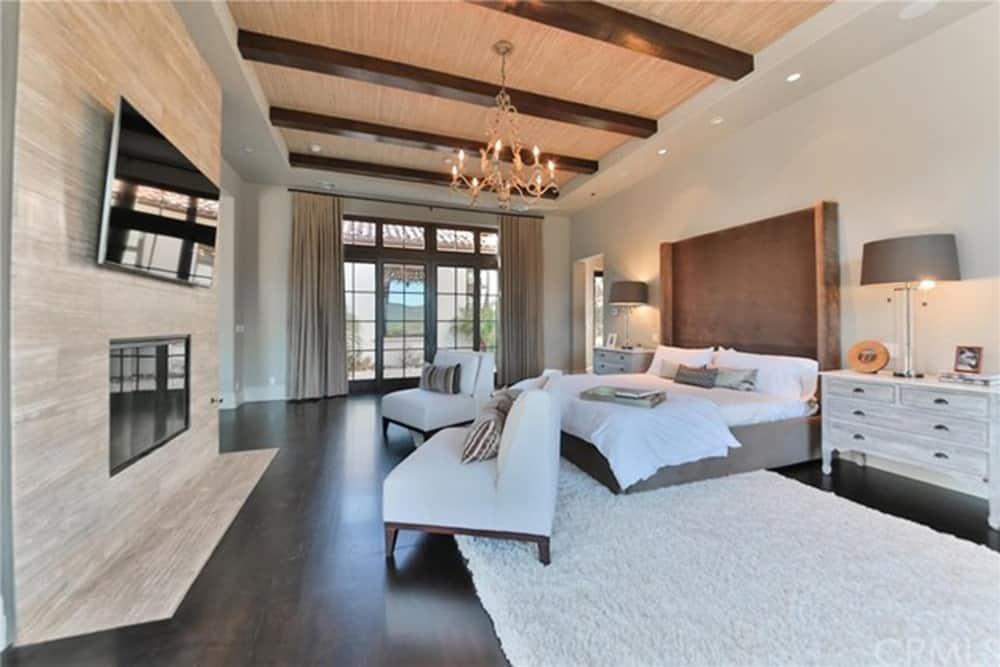 Một đèn chùm nến lạ mắt chiếu sáng phòng ngủ chính này trưng bày một chiếc giường bằng vải nhung với khu vực tiếp khách ở cuối cùng với lò sưởi và TV treo tường.