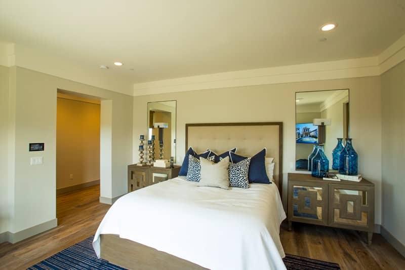 Phòng ngủ đơn giản với gương và một chiếc giường búi nằm trên tấm thảm sọc xanh. Nó bao gồm đầu giường đầy phong cách đứng đầu với giá nến và bình hoa mờ.