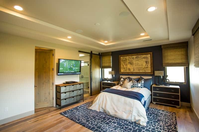 Phòng ngủ này có tác phẩm nghệ thuật cổ điển và một chiếc giường ấm cúng nằm cạnh đầu giường và cửa sổ hình ảnh.  Nó có một bức tường màu xanh đậm và trần nhà được gắn đèn chiếu sáng.