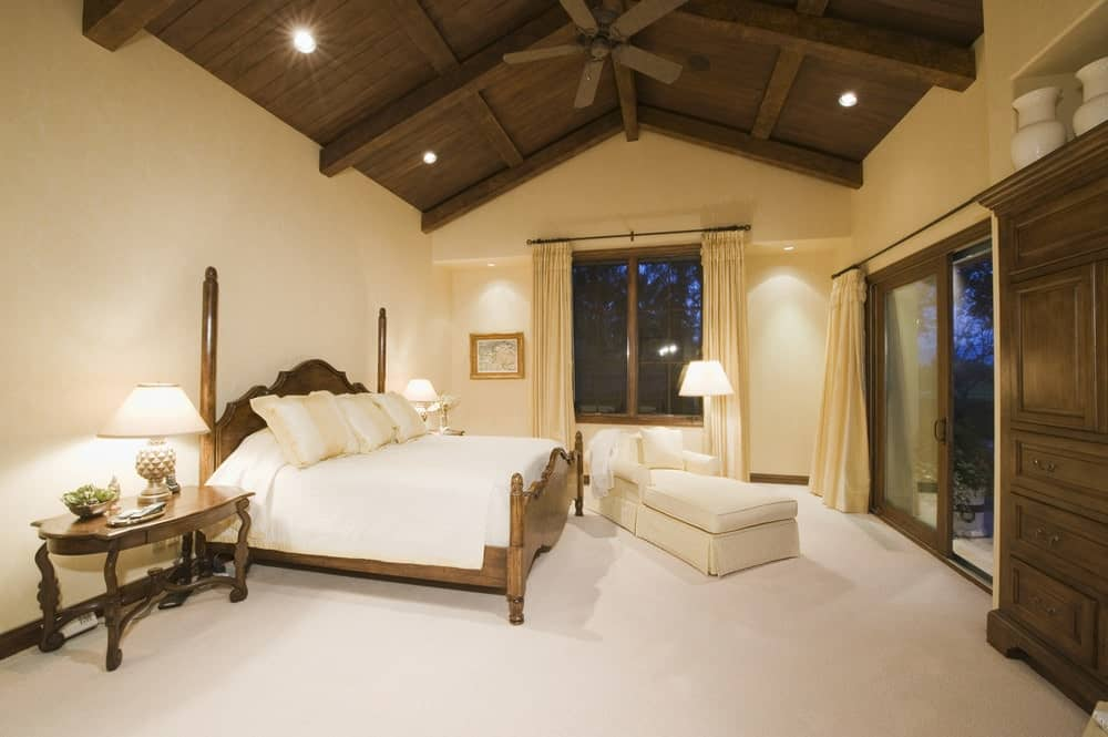 Một phòng chờ chaise mặc váy nằm gần giường hai tấm gỗ trong phòng ngủ màu be này với thảm trải sàn và trần nhà hình vòm trong các tấm ván gỗ tối màu.
