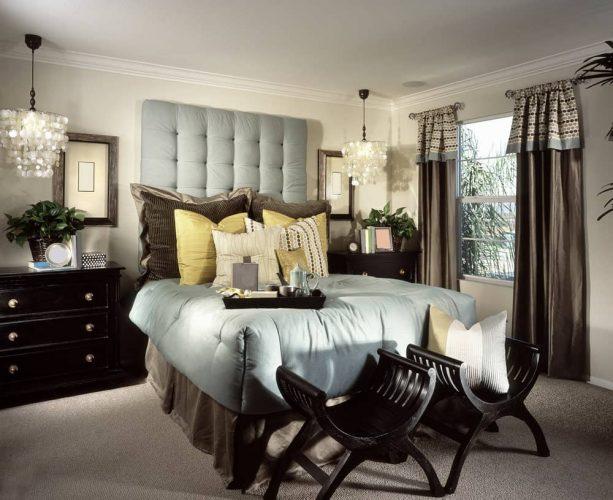 Đèn chùm vỏ treo trên đầu giường bằng gỗ tối màu với một chiếc giường chần màu xám ở giữa chứa đầy gối ấm cúng và khay giường màu đen.