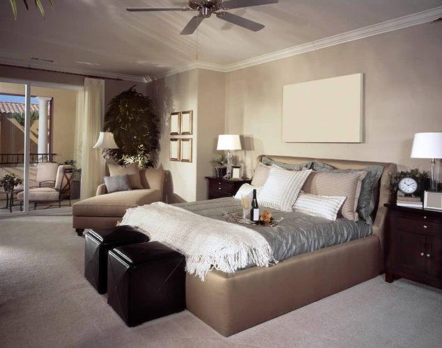 Phòng ngủ chính màu be với đầu giường bằng gỗ tối màu và giường bọc nệm đi kèm với một phòng chờ chaise phù hợp và ottoman đen.