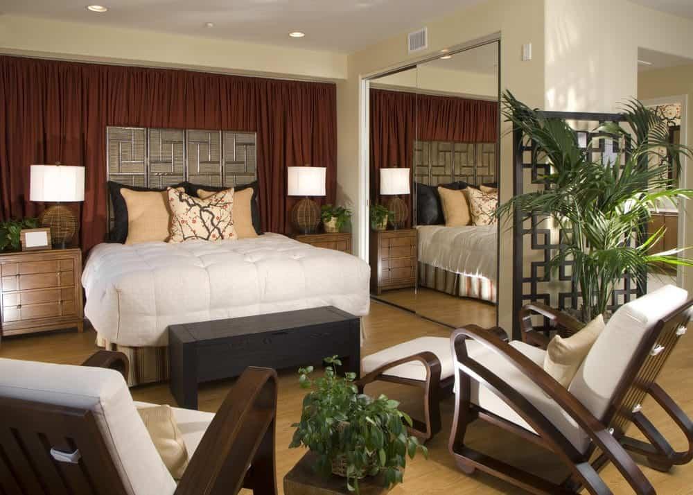 Màn Burgundy đặt một phông nền sang trọng cho chiếc giường đầy phong cách kèm theo đầu giường bằng gỗ và băng ghế dự trữ. Nó bao gồm ghế phòng chờ màu trắng và tủ quần áo tích hợp với cửa kính tạo ra một không gian thị giác lớn cho căn phòng.