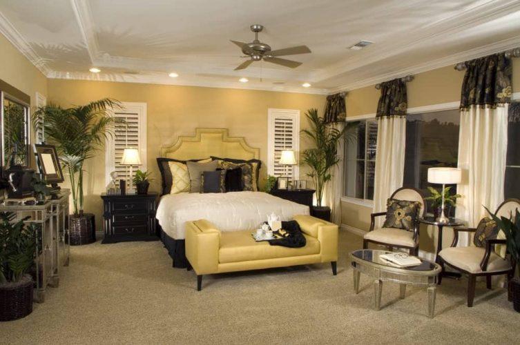 Cây trồng trong chậu cao tạo cảm giác nhiệt đới trong phòng ngủ chính này với giường bọc nệm và ghế dài kèm theo đầu giường bằng gỗ tối màu và ghế đệm.