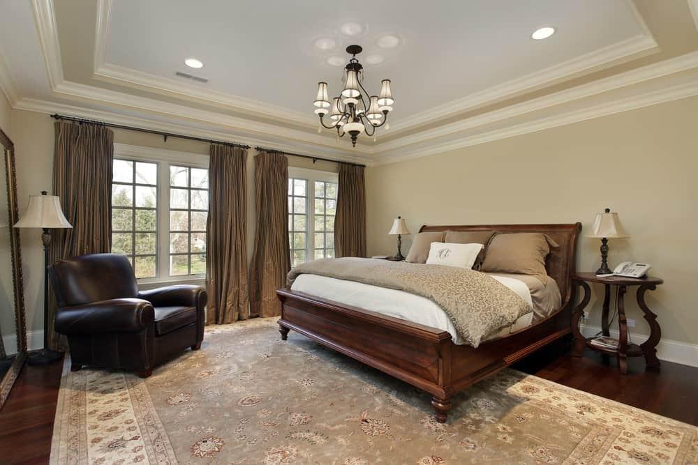 Một đèn chùm tuyệt đẹp chiếu sáng phòng ngủ màu be cổ điển này cung cấp một chiếc giường gỗ và ghế bành bọc da trên một tấm thảm hoa.