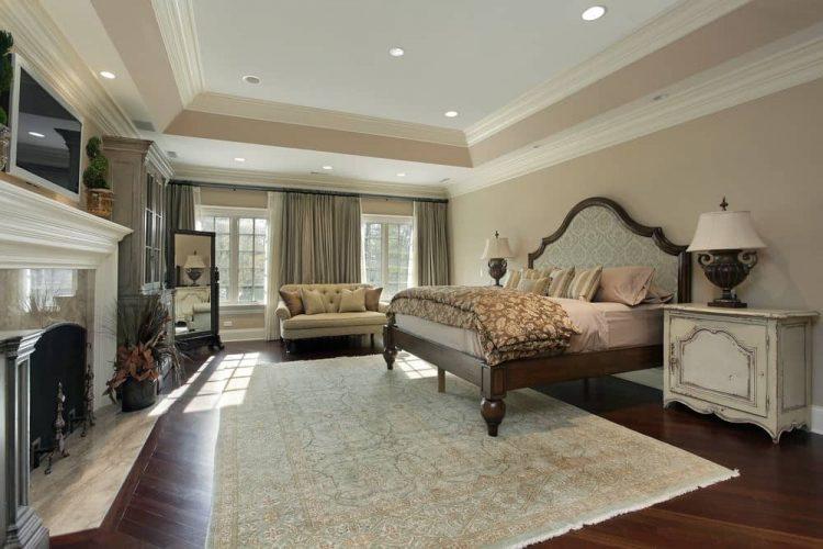 Luồng ánh sáng tự nhiên xuyên qua các cửa sổ có khung màu trắng trong phòng ngủ chính này với lò sưởi bằng đá cẩm thạch và giường gỗ nằm giữa đầu giường đau khổ.