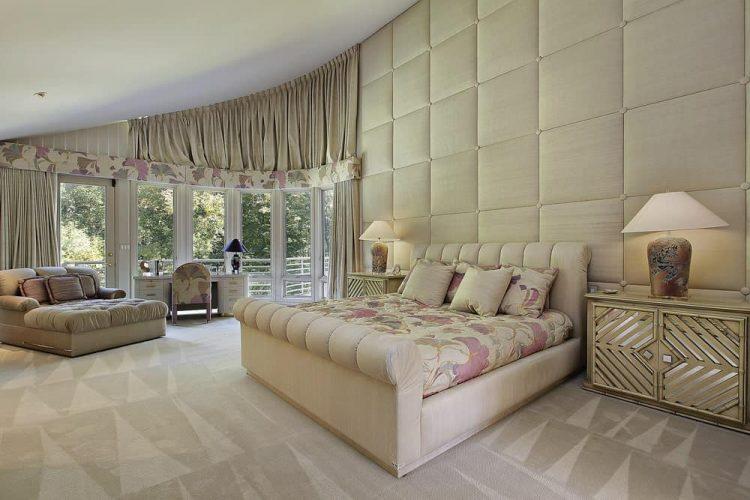 Một chiếc giường bọc nệm trong bộ đồ giường hoa làm tăng thêm điểm nhấn quyến rũ trong phòng ngủ sang trọng này với một phòng chờ quá khổ và đầu giường được nhân đôi đặt trên bức tường chần.