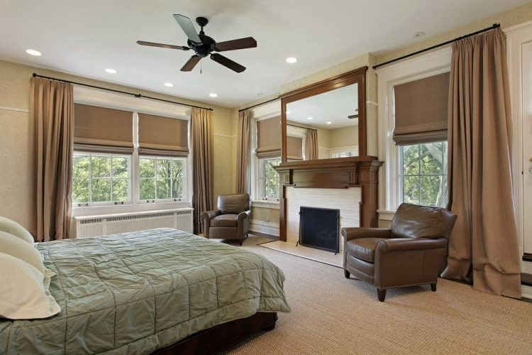 Phòng ngủ màu be với một chiếc giường thoải mái được bọc trong một chiếc chăn màu xanh lá cây xô thơm đối diện với lò sưởi bên cạnh cửa sổ có khung màu trắng và ghế bành bọc da màu nâu.
