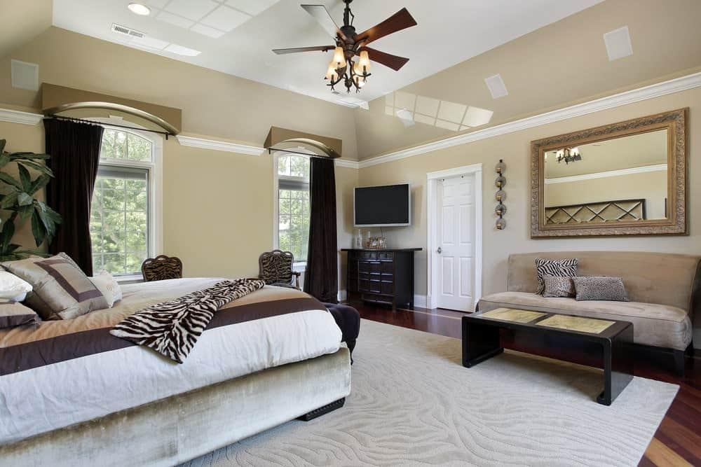 Phòng ngủ trang nhã với giường và ghế sofa bằng nhung đi kèm với gương trang trí công phu và bàn cà phê bằng gỗ tối màu.  Nó có cửa sổ bằng kính và sàn gỗ cứng đứng đầu bởi một tấm thảm khu vực kết cấu.