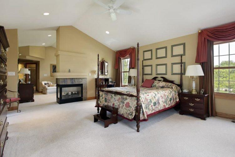 Một phòng ngủ lớn với sàn trải thảm và cửa sổ đóng khung bằng gỗ được trang trí bằng rèm màu nâu và diềm màu đỏ.  Nó bao gồm một giường bốn poster và một khu vực chỗ ngồi phía sau lò sưởi ba mặt.