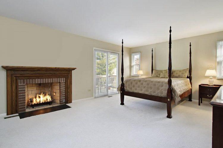 Phòng ngủ đơn giản với một chiếc giường bốn cọc và lò sưởi bằng gạch được đóng khung trong một lớp phủ gỗ tự nhiên.  Nó có thảm trải sàn và thanh trượt kính dẫn ra ban công.