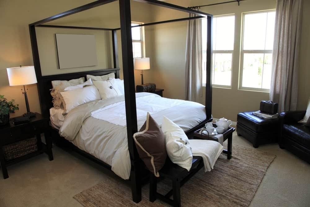 Một cái nhìn cận cảnh về phòng ngủ chính này với ghế da màu đen và giường tán bổ sung cho đầu giường bằng gỗ tối màu và băng ghế ngồi trên một tấm thảm đay.