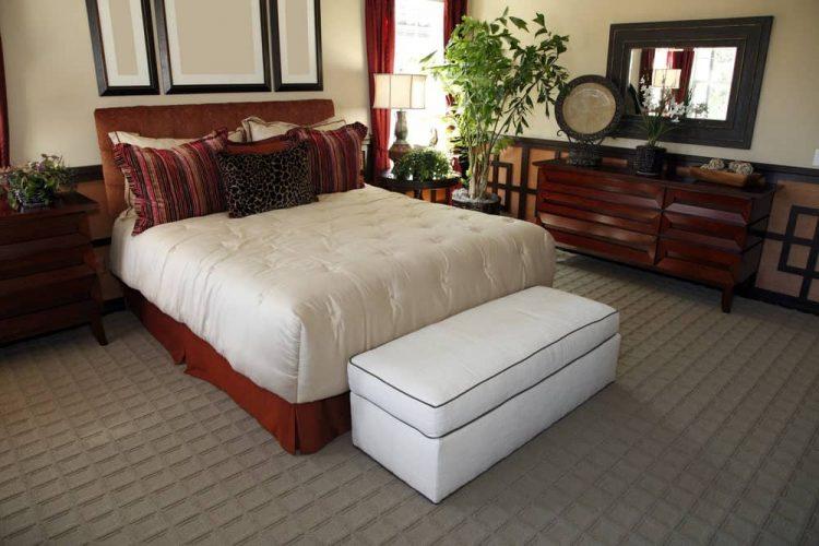 Một chiếc gương có khung bằng gỗ treo phía trên bàn điều khiển đặt trên bức tường được ốp sành điệu.  Có một chiếc giường với một băng ghế dự trữ màu trắng trên đầu của nó trên sàn thảm kết cấu.