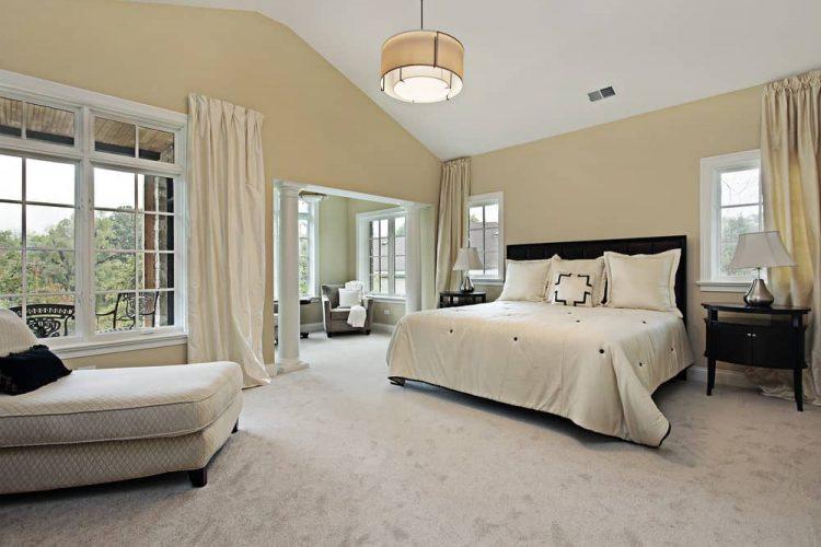 Phòng ngủ rộng rãi tự hào có ghế bành nhung và phòng chờ có hoa văn đối diện với giường gỗ tối màu được chiếu sáng bởi đèn bàn mạ crôm và đèn treo trống.