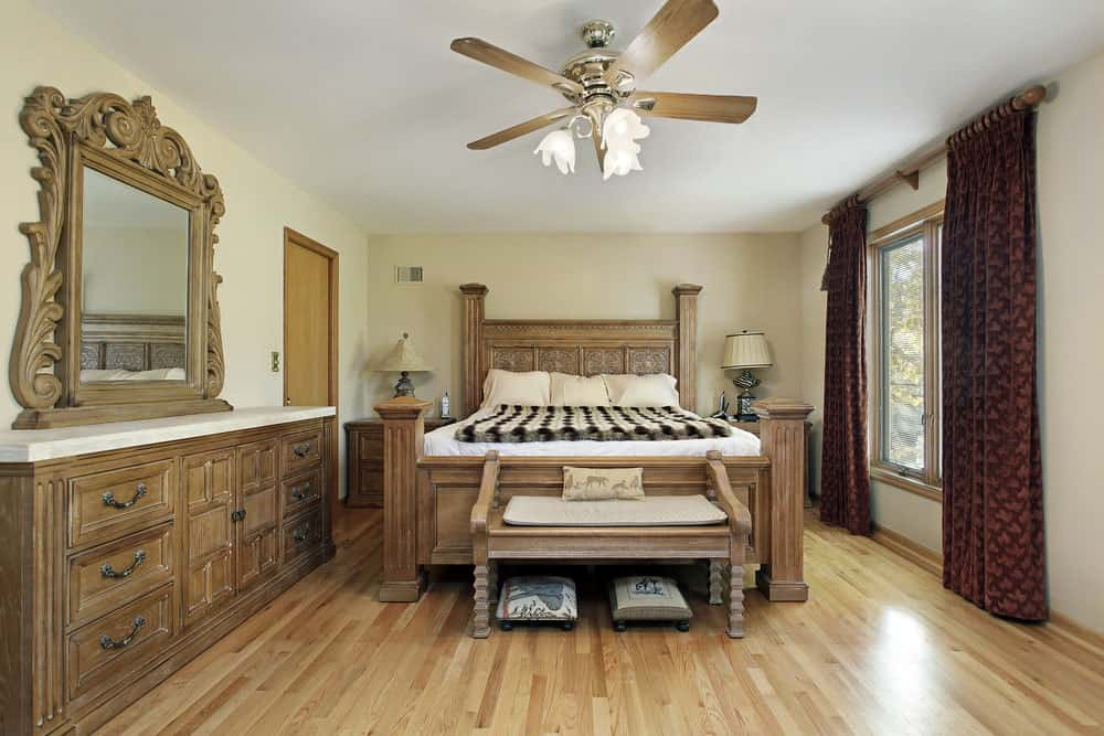 Rèm cửa màu đỏ tía nổi bật trong phòng ngủ màu be này với quạt trần đáng yêu và đồ nội thất bằng gỗ tự nhiên hòa quyện với sàn gỗ cứng.