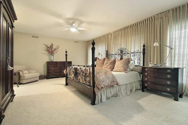 Đầu giường bằng gỗ tối màu bổ sung cho tủ quần áo và tủ quần áo đứng đầu với một bình hoa chrome.  Phòng này có bốn giường áp phích trang trí công phu được làm nổi bật với gối hoa và chăn bông.