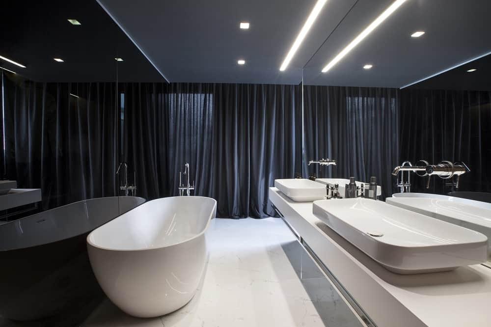 Phòng tắm chính này có bồn tắm trên sàn lát gạch trắng, bàn trang điểm chìm tàu đôi với gương lớn và một tấm màn đen.