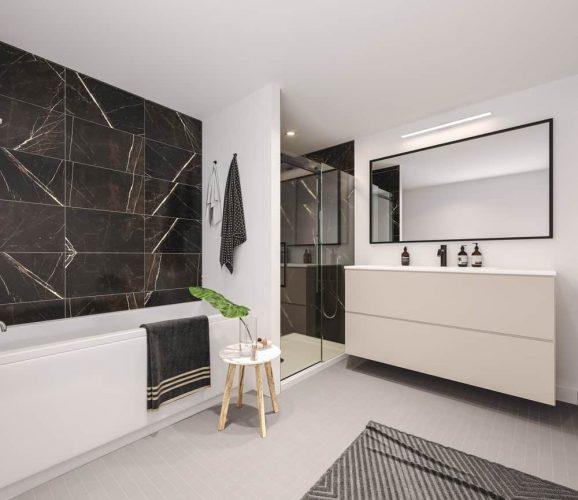Một vòi hoa sen bước vào bên trong bàn trang điểm nổi trong phòng tắm chính này. Nó cũng có một bồn tắm góc với những bức tường gạch đen và một tấm gương lớn.