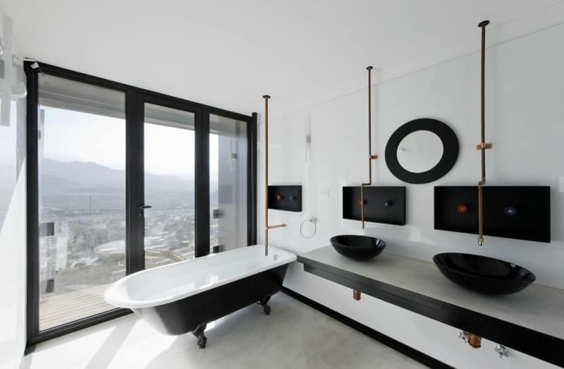 Phòng tắm chính này có một bàn trang điểm màu đen nổi treo bên cạnh bồn tắm móng vuốt và một chiếc bình cao trên sàn lát gạch.
