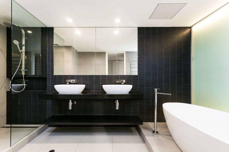 Phòng tắm chính có một hỗn hợp tương phản cao của các tông màu, với bức tường lát gạch màu đen trên nền gạch màu be lớn màu trắng ngoài trời, cộng với bồn rửa chân màu trắng và bồn rửa tàu.  Vanity màu đen nổi treo bên cạnh một vòi hoa sen lớn bao quanh bằng kính.