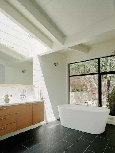 Phòng tắm chính này có bồn tắm hiện đại trên sàn gạch đen và cửa trượt dẫn ra vườn.  Nó cũng có những bức tường trắng với một tấm gương lớn.