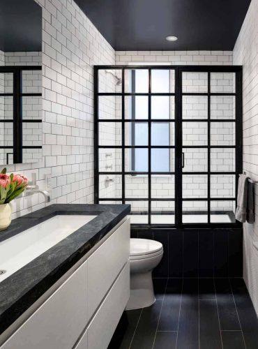 Phòng tắm chính kiểu công nghiệp có nhà vệ sinh và vòi sen không cửa ngăn được đóng trong cửa khung nhôm màu đen. Nó bao gồm một vanity chìm nổi phù hợp với sàn gỗ cứng và sơ đồ gạch tàu điện ngầm trắng.