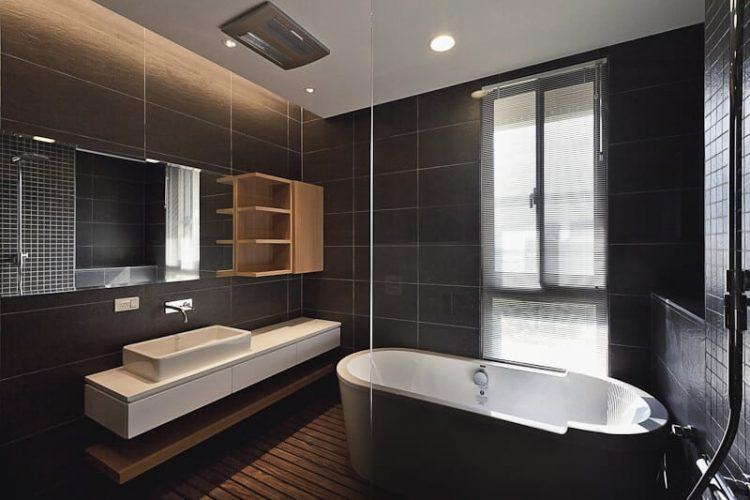 Phòng tắm nổi bật trong nhà, với tông màu tối hơn nhờ sàn gỗ cứng màu và gạch ốp tường khổ lớn. Kệ gỗ tự nhiên và bàn trang điểm màu trắng đứng đối diện với bồn tắm lớn có màu nâu với nội thất màu trắng.
