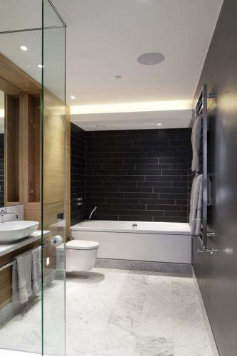Phòng tắm chính có tông màu sáng lịch sự với sàn gỗ cứng màu và bồn tắm góc với gạch ốp tường khổ lớn màu đen.