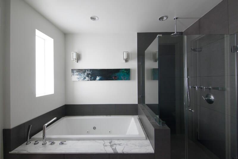 Vòi hoa sen toàn kính và bồn tắm bể sục lớn được bọc trong gạch màu xám bên dưới cửa sổ, bức tranh và tranh treo tường.