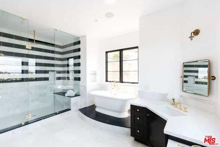 Phòng tắm chính này có gạch trắng và tường trắng có cửa sổ với tầm nhìn tuyệt vời ra bên ngoài.  Nó cũng có một bồn tắm trên đá cẩm thạch đen và tủ màu đen.