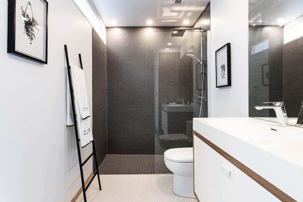 Một phòng tắm tuyệt đẹp với một nhà vệ sinh truyền thống trên gạch lát sàn màu trắng với vòi hoa sen cửa kính đứng trên sàn nhà màu đen và gạch ốp tường.