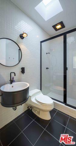 Một phòng tắm với một nhà vệ sinh truyền thống trên gạch lát sàn màu đen và một vòi solo với gương tròn nhỏ trên các bức tường trắng.  Nó cũng có cửa kính trượt dẫn đến khu vực tắm.