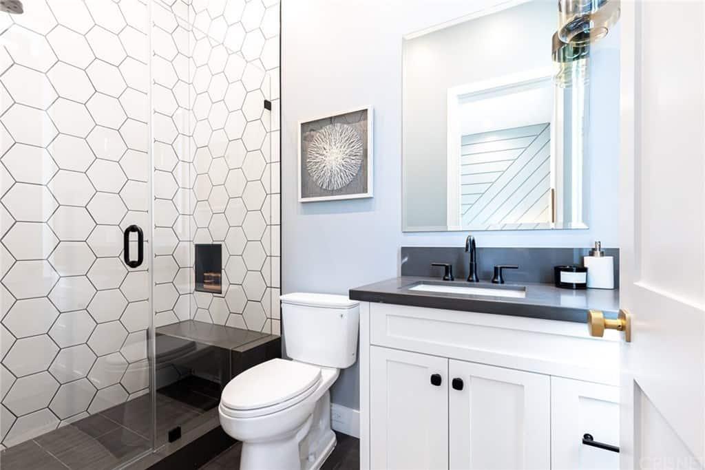 Phòng tắm màu đen và trắng tương phản với sàn gạch khổ lớn màu tối, với vòi hoa sen bao quanh bằng kính và bàn trang điểm với tủ kính hun khói.