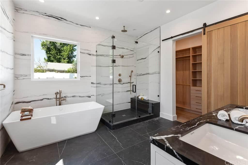 Phòng tắm chính hiện đại có bồn tắm độc lập được bổ sung và vòi sen không cửa ngăn được đặt trong cửa kính.