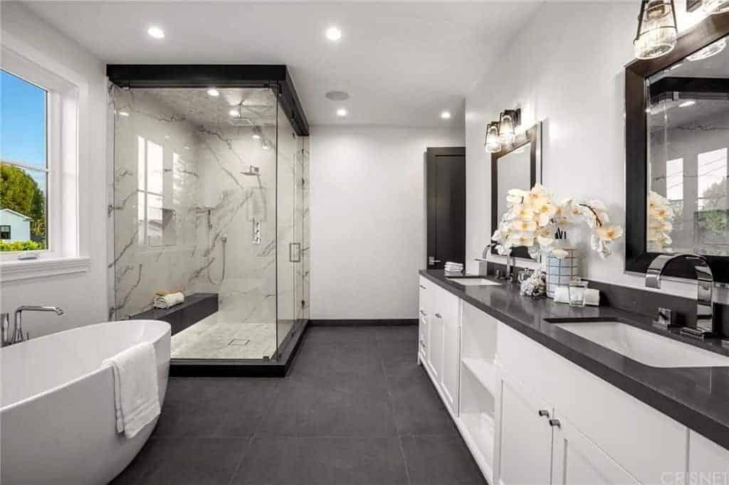 Một phòng tắm chính cổ điển chứa đầy vòi hoa sen đi bộ và bàn trang điểm đứng trên bồn rửa tàu. Nó cũng có một tấm gương được gắn cố định vào bức tường trắng.