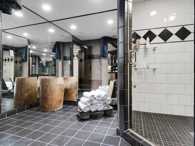 Phòng ngủ chính này có vòi sen không cửa ngăn và gương lớn.  Phòng này cũng có gạch lát sàn màu đen kết hợp với tường gạch trắng.