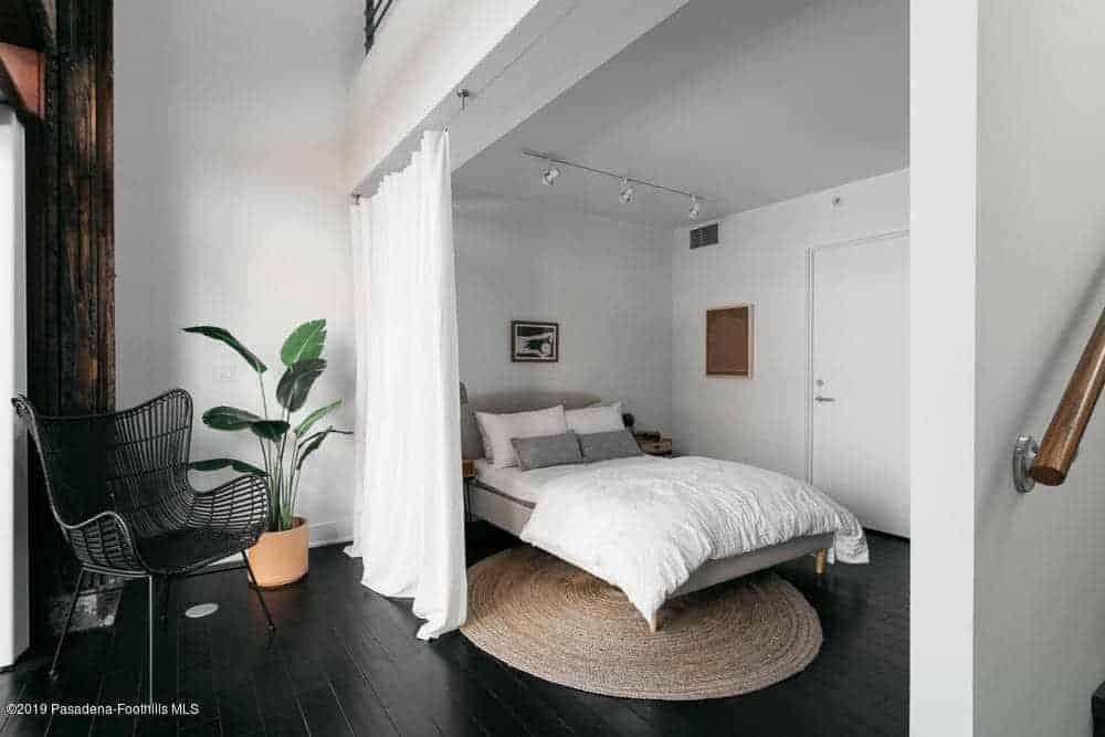 Phòng ngủ này có giường màu trắng đặt trên thảm tròn. Nó có rèm cửa màu trắng và ghế màu đen hiện đại.