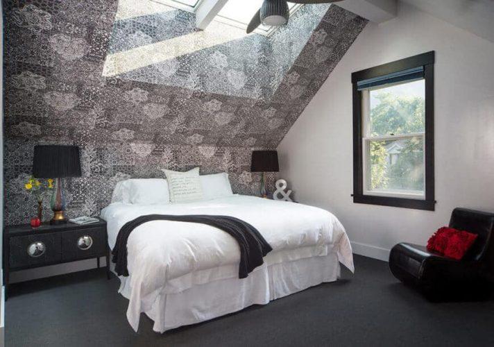 Phòng tắm chính có trần nhà hình vòm với giếng trời lớn, lấp đầy không gian màu xám với ánh sáng tự nhiên. Một cửa sổ lớn hiện ra trên chiếc ghế da màu đen cong.