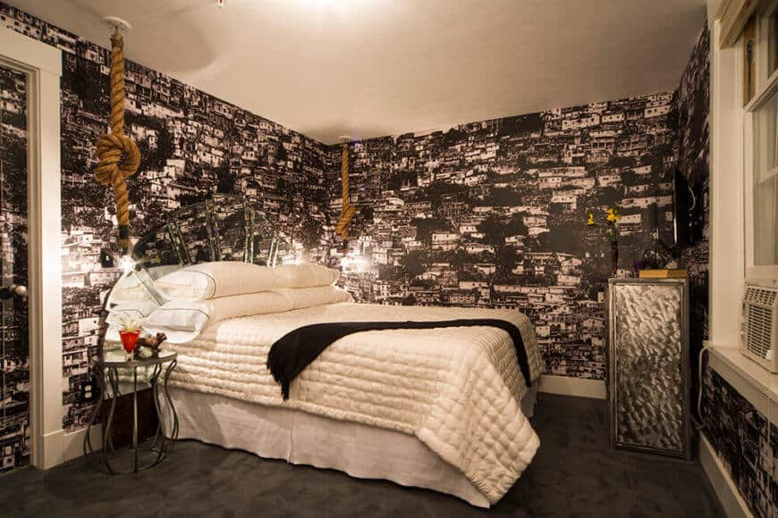 Phòng ngủ này được bọc trong giấy dán tường Favela, tạo ra một kết cấu sắc nét với cảm giác vui tươi, mặc dù bảng màu đen và trắng.
