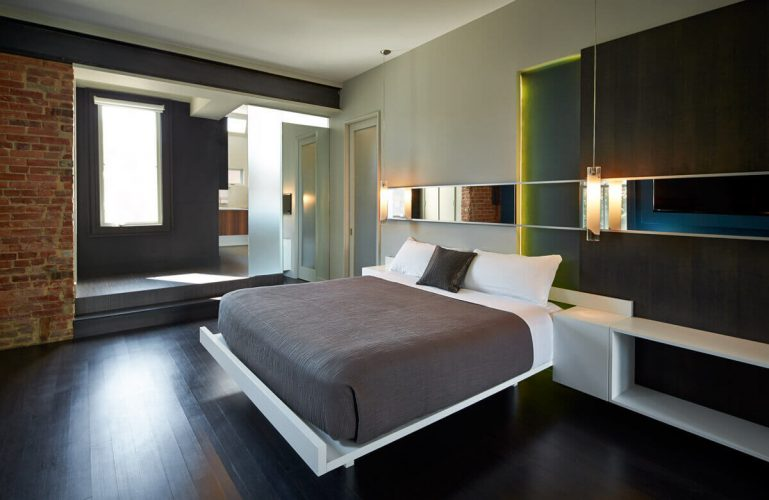 Phòng ngủ chính này có phòng ngủ ấm cúng trên sàn gỗ cứng màu đen phù hợp với các bức tường màu đen.