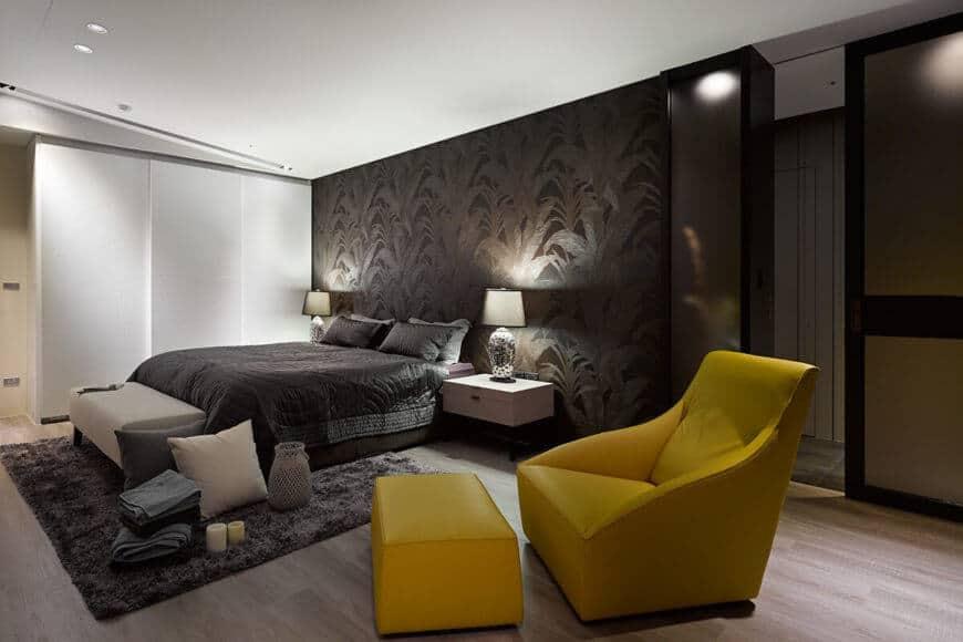 Chiếc giường được đặt cạnh một cặp bàn trang điểm màu trắng bóng, với một chiếc ghế dài màu xám hiện đại dưới chân.  Ghế màu vàng đậm và ottoman được bọc da theo phong cách hiện đại tối giản.