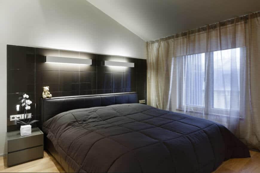 Phòng ngủ chính có kiểu dáng đẹp và hấp dẫn. Một chiếc giường cỡ King là trung tâm của sự chú ý với đầu giường khổng lồ cung cấp không gian lưu trữ và ánh sáng dịu. Sàn gỗ cứng tự nhiên tương phản với màu tối của tấm và đầu giường.