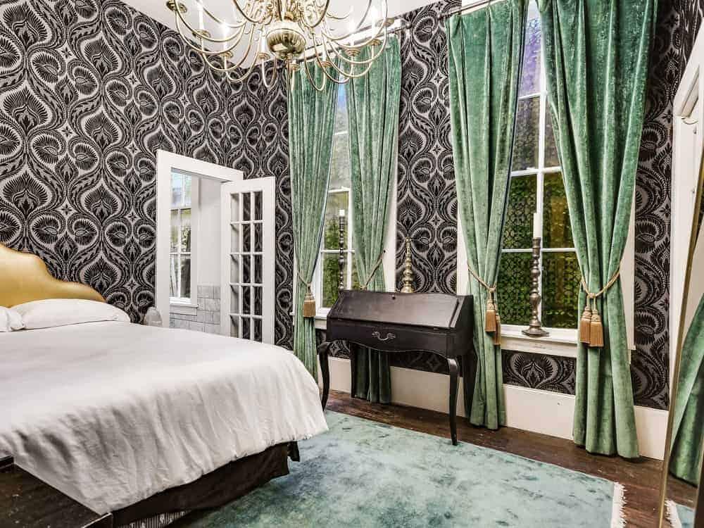 Phòng ngủ chính này có tường thiết kế màu đen và trắng và một chiếc giường thoải mái trên tấm thảm. Nó cũng có một đèn chùm nến tuyệt đẹp.