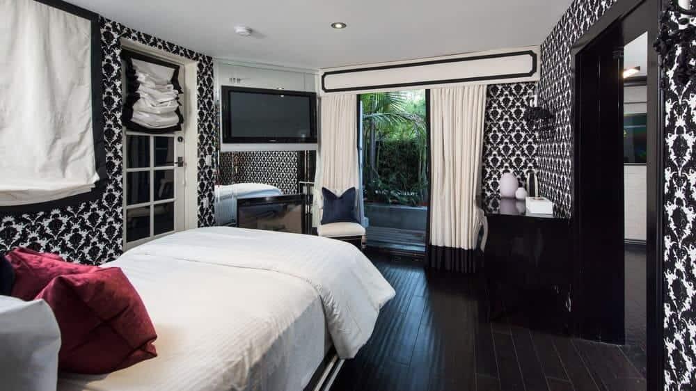 Giấy dán tường được thiết kế màu đen và trắng hấp dẫn của căn phòng này bổ sung cho sàn gỗ cứng xỉn.  Những thứ này làm cho tấm trải giường màu trắng đứng đối diện với ống khói và TV.