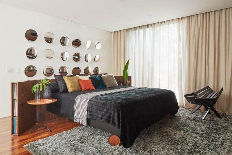 Phòng ngủ chính đáng yêu này có một tấm thảm màu xám đậm bao phủ hầu hết các sàn gỗ cứng.  Điều này rất phù hợp với chiếc giường màu đen và chiếc ghế màu đen ở bên cạnh để nổi bật trên bức tường trắng và trần nhà màu trắng.