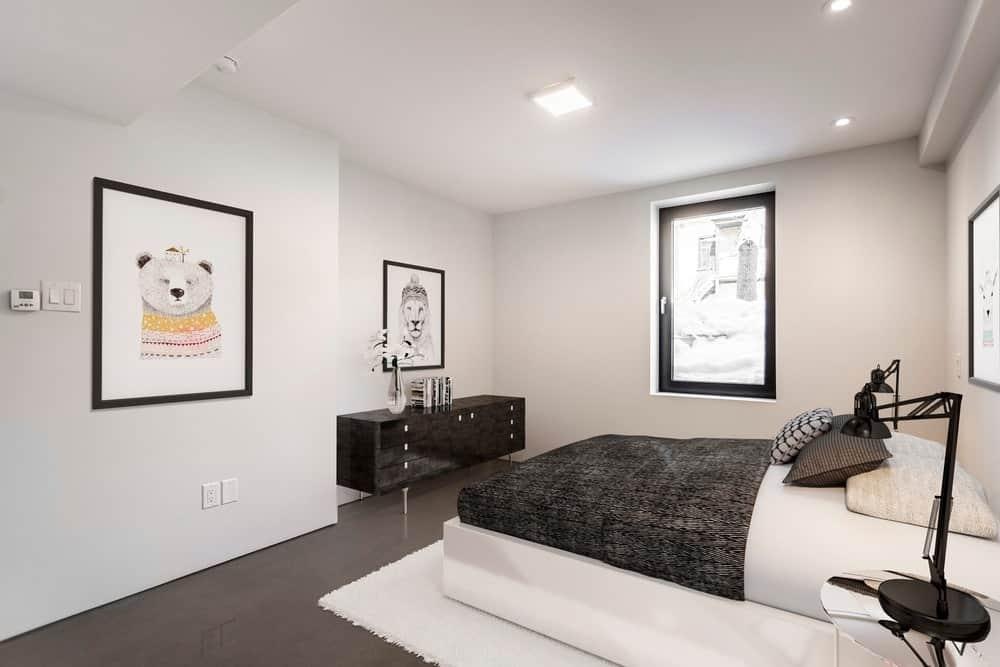 Phòng ngủ này có sàn màu đen tuyệt đẹp phù hợp với tủ cao đến thắt lưng ở góc cũng như tấm trải giường và gối của giường.  Chúng sau đó được làm sáng bởi các bức tường và trần nhà màu trắng với ánh sáng lõm.