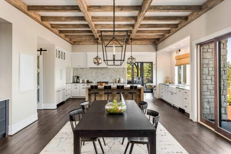 Phong cách trang trại nội thất không gian mở với trần chùm và đèn công nghiệp trên bàn ăn và đảo ăn sáng.