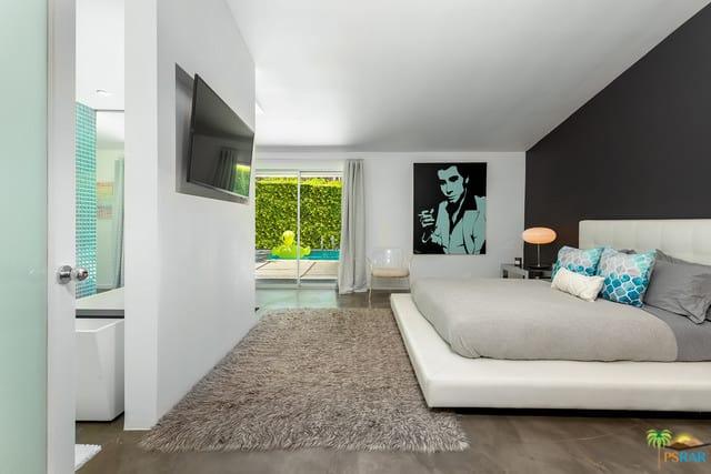 Giường nền màu trắng của phòng ngủ chính này tương phản với bức tường màu đen đằng sau nó cũng như bức tranh màu đen ở bên cạnh.